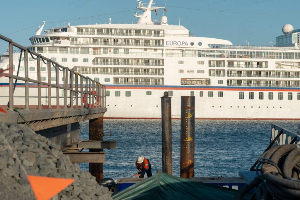 A photo of a cruise ship passing in front of the cruise ship terminal construction site